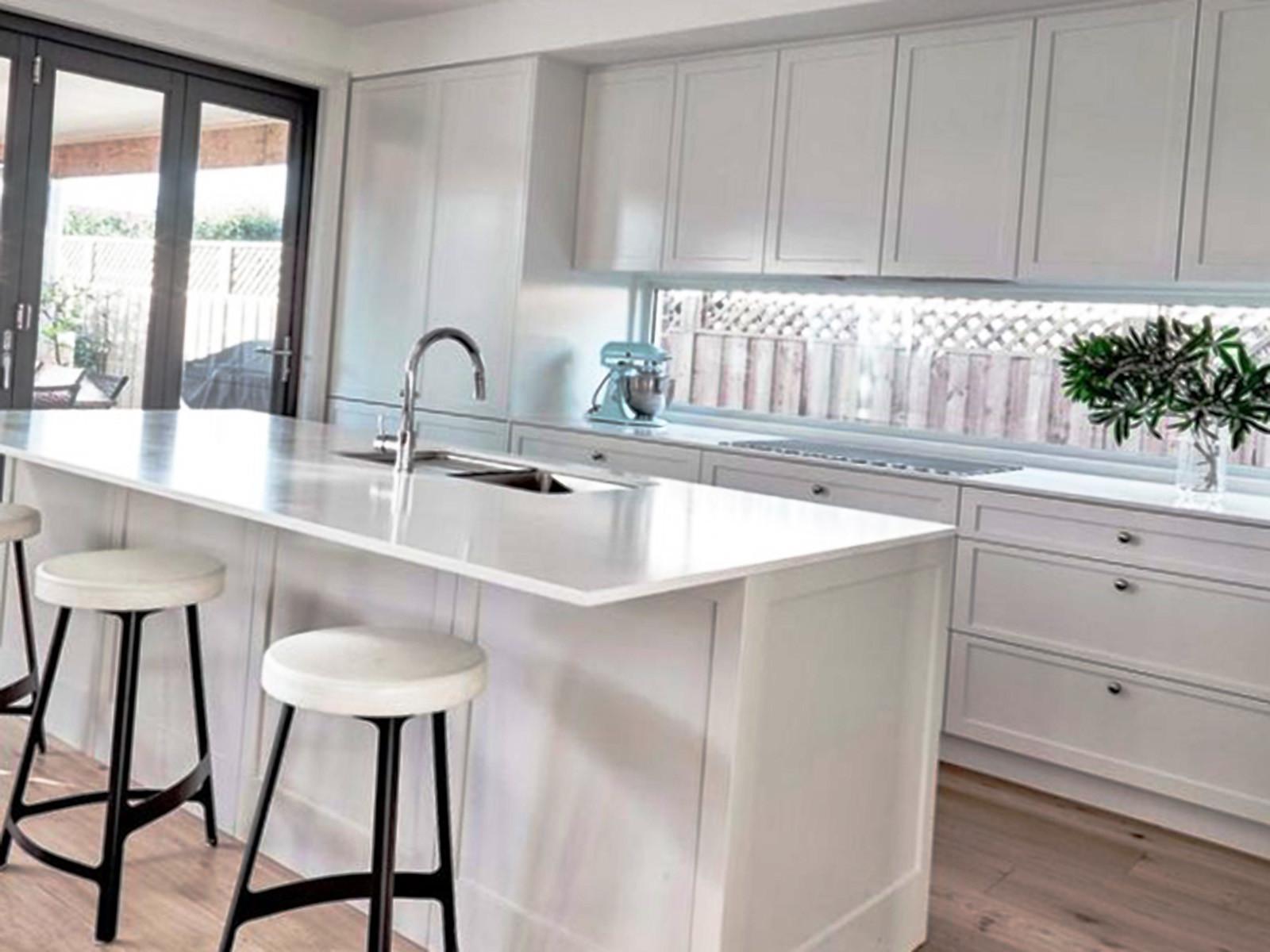Кухонный остров белого цвета с табуретками