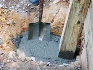 Заливаем вертикальные столбы перголы раствором бетона