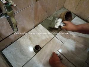 Укладка кусков кафеля на пол в ванной комнате